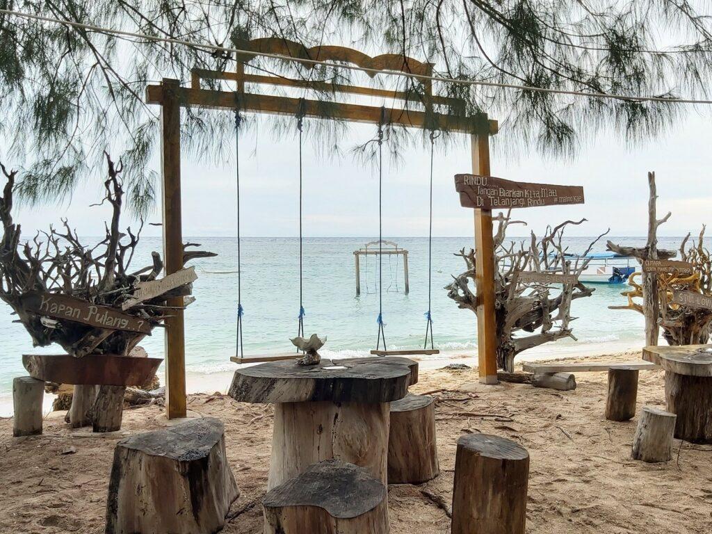 Area bersantai tempat duduk dan ayunan di tepi pantai
