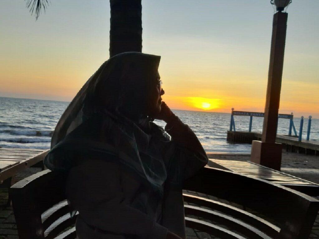 Bersantai menikmati momen sunset di tepi pantai