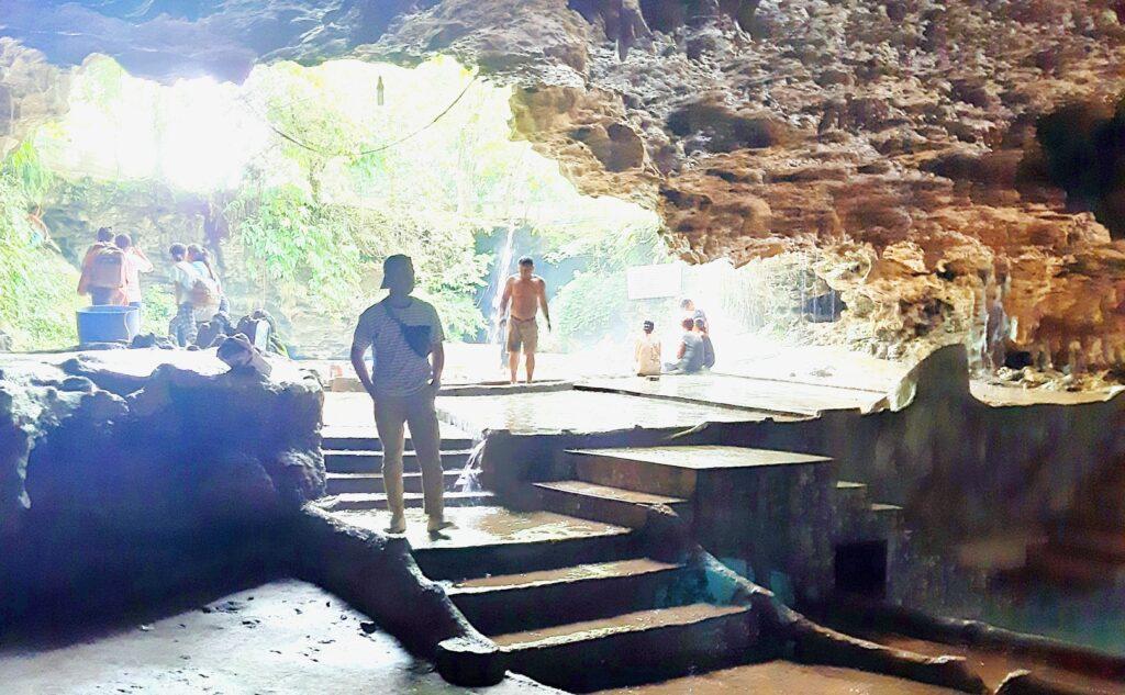 pengunjung di dalam gua di depan kolam air panas