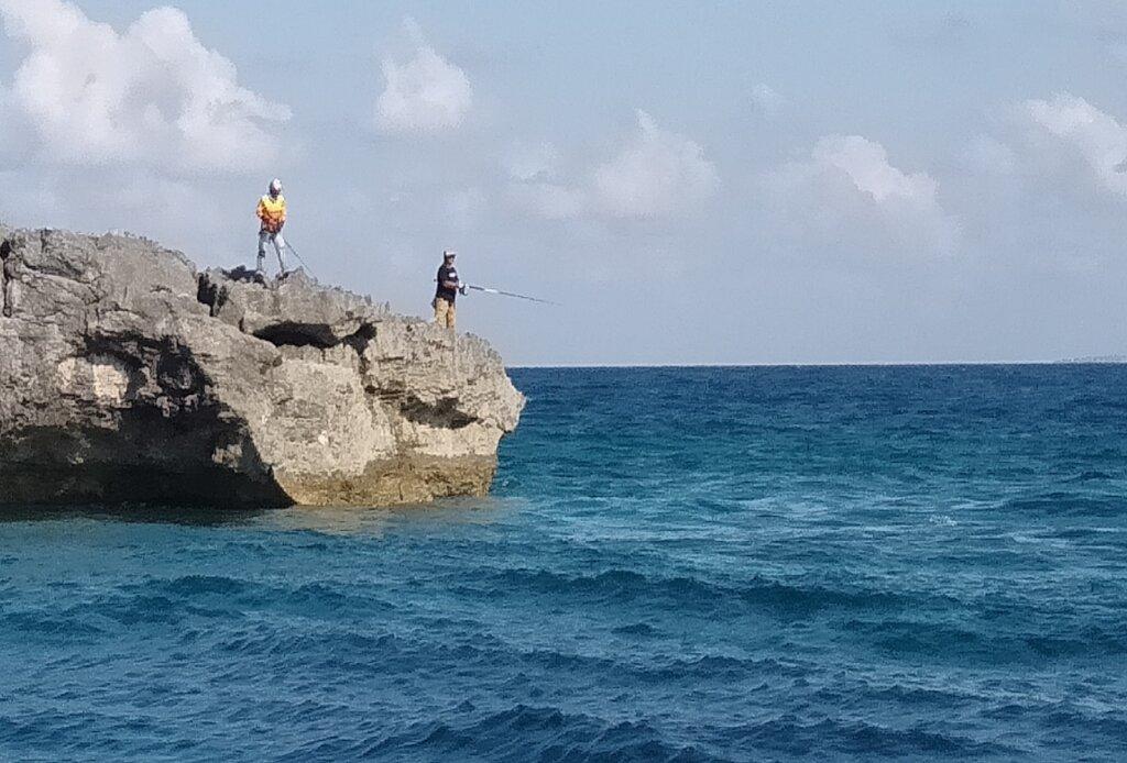 wisatawan memancing di atas karang sektiar pulau
