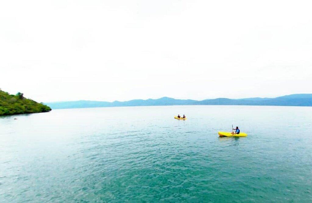 wisatawan sedang mengarungi danau menggunakan kano
