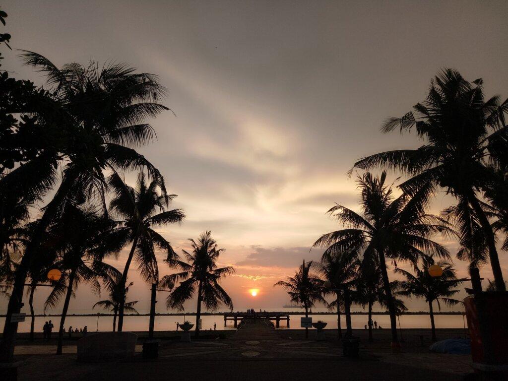 menikmati golden sunset di tepi pantai