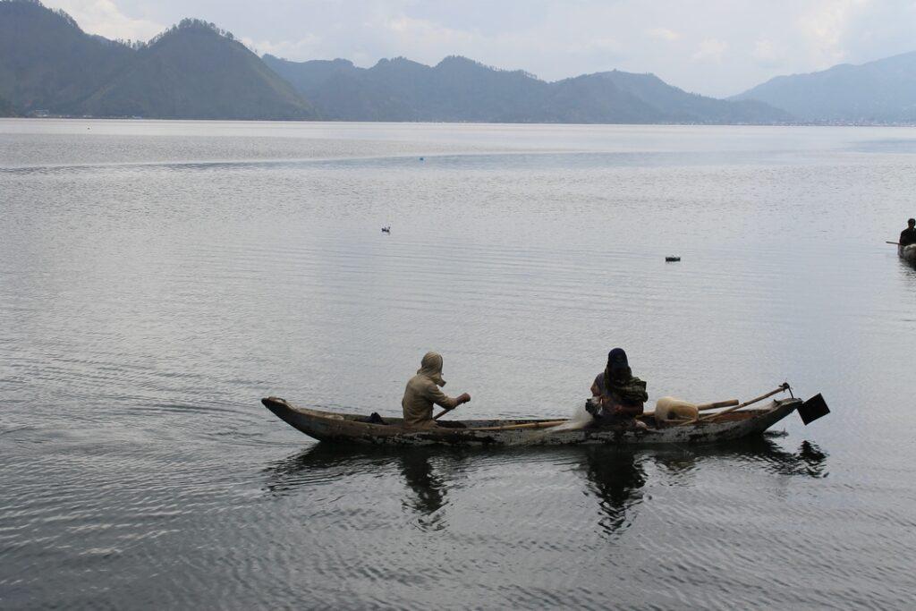 Pengunjung sedang bermain perahu rakit di Danau Lau Kawar
