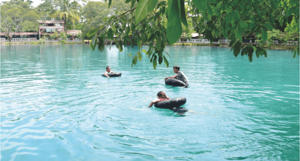 Pengunjung berenang di pinggir danau