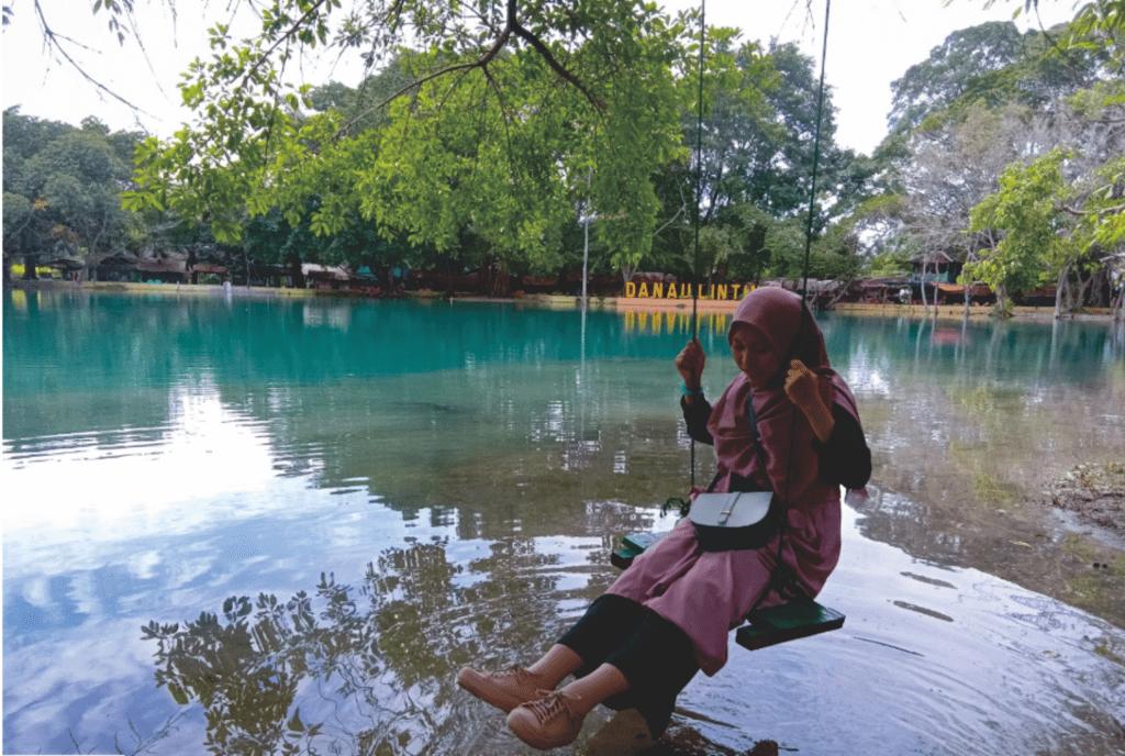 Pengunjung bermain ayunan di tepi Danau Linting