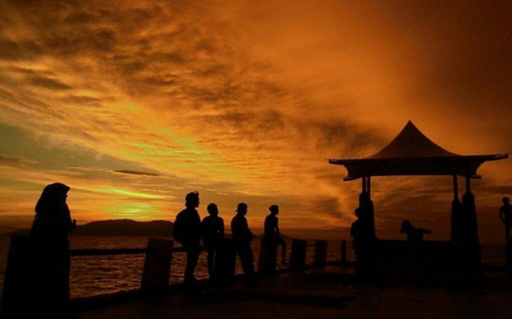 wisatawan menikmati senja di tepi pantai