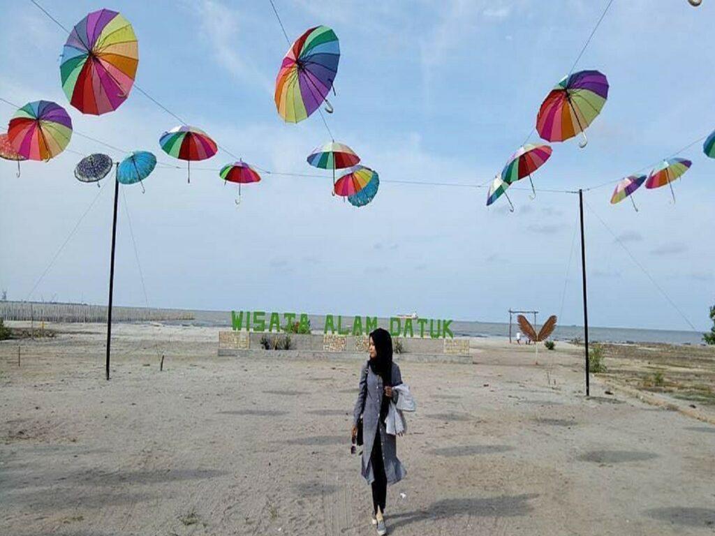 area tepi pantai dengan hiasan payung warna-warni
