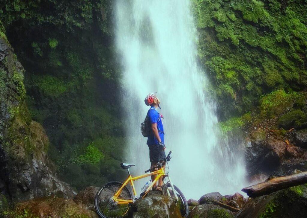 pengunjung bersepeda ke lokasi air terjun