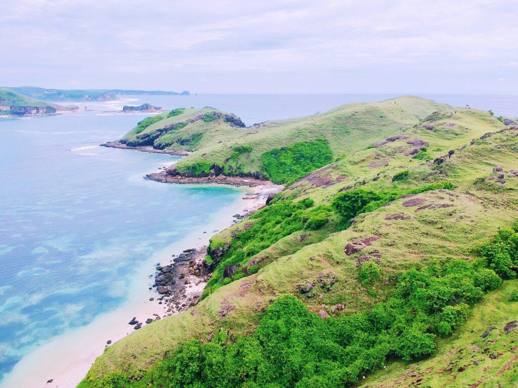 kawasan perbukitan hijau dengan pemandangan pantai dan laut