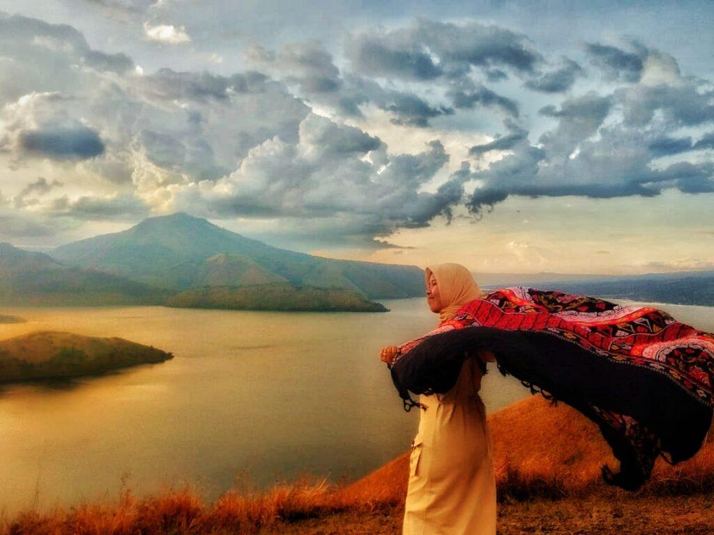 Pengunjung tengah berfoto dengan latar Danau Toba di area perbukitan