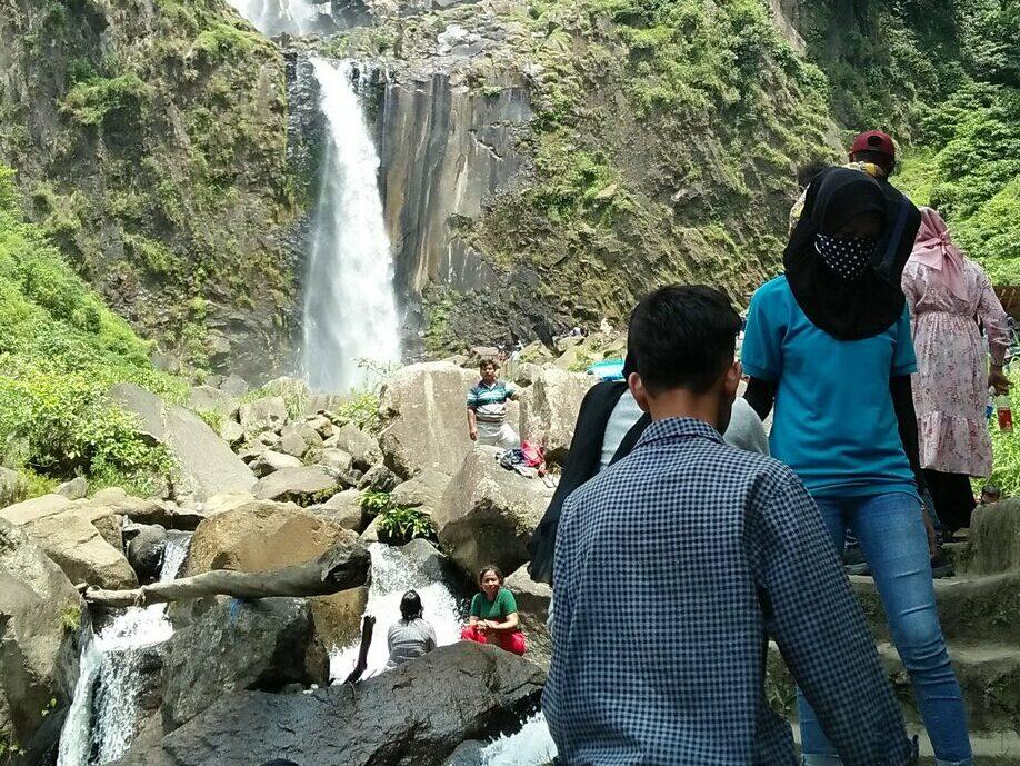 pengujung sedang menapaki anak tangga menuju air terjun