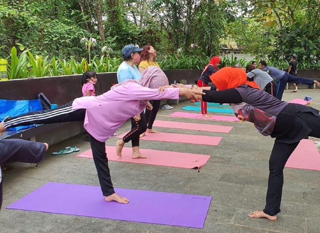 Aktivitas senam lantai dan yoga di area taman