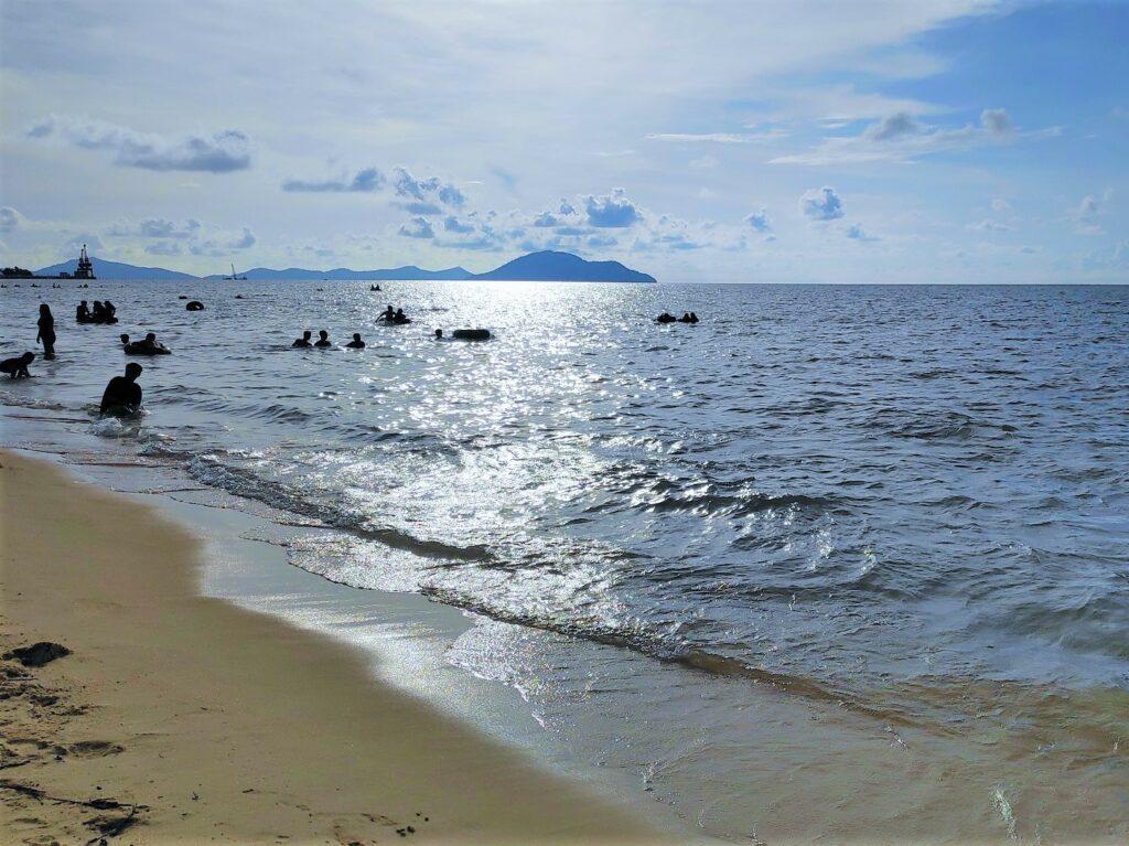 Wisatawan bermain di pantai tepi laut