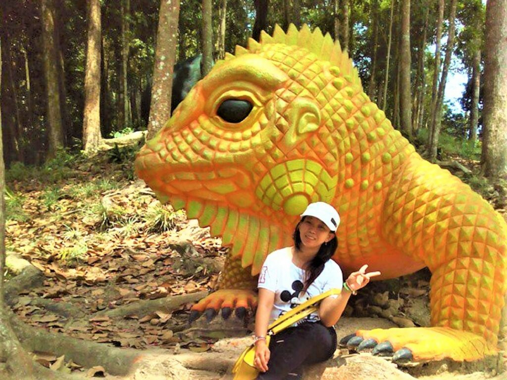 Berfoto bersama patung Iguana di area objek wisata