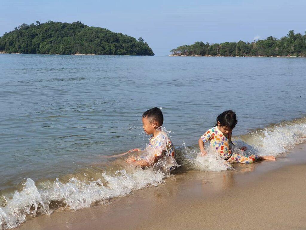 anak-anak sedang bermain air di tepi pantai