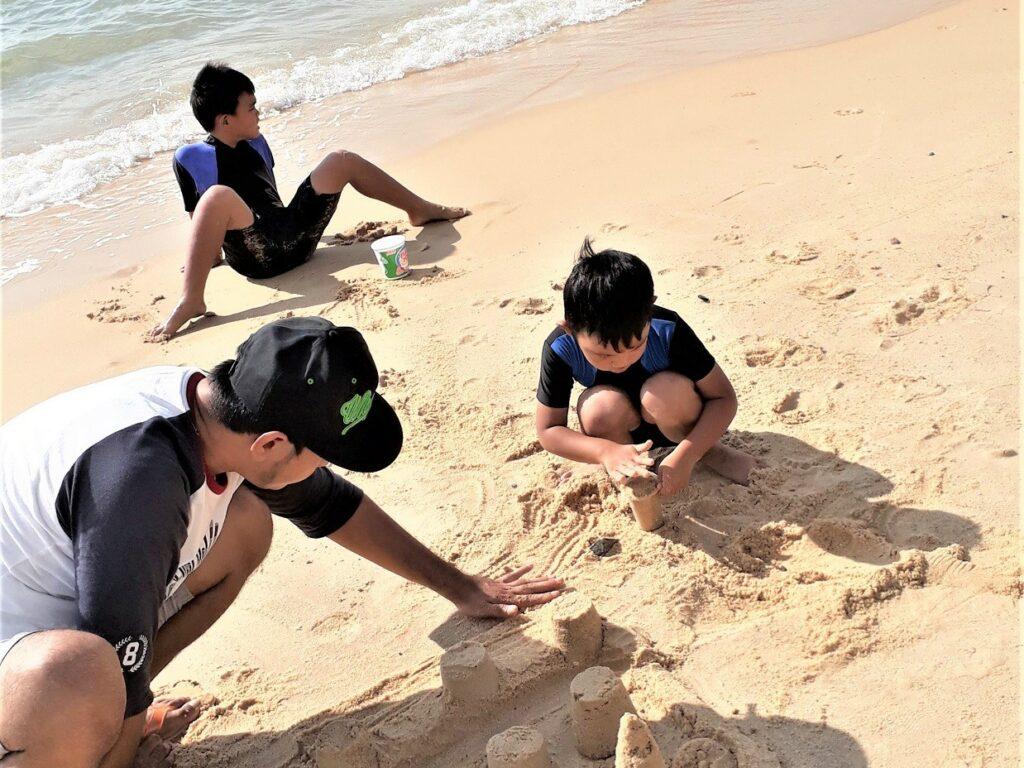 wisatawan bermain pasir di tepi pantai pasir panjang