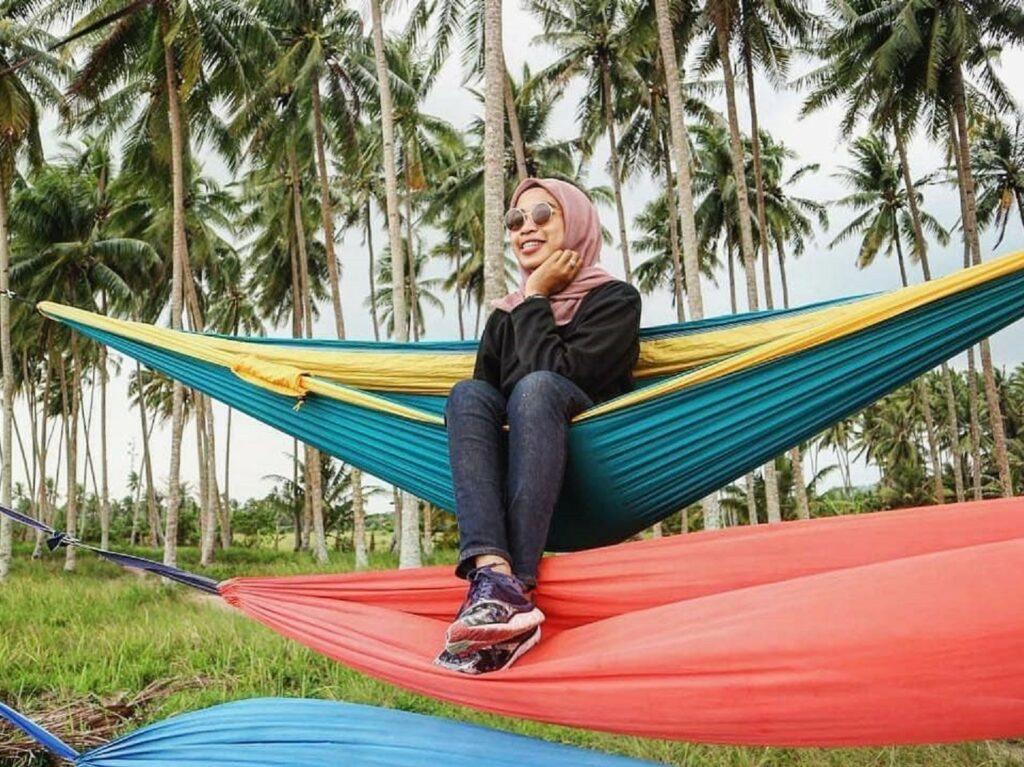 wisatawan bersantai di wahana hammock tepi pantai