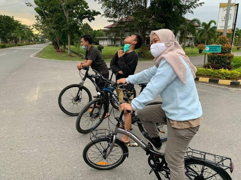 pengunjung bersepeda di sekitar taman