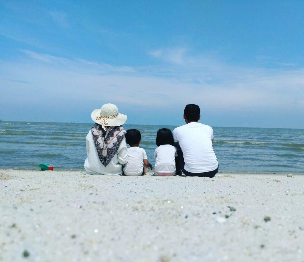 Sebuah Keluarga tengah berfoto bersama berlatarkan birunya langit dan beralaskan putihnya pasir Sri Mersing