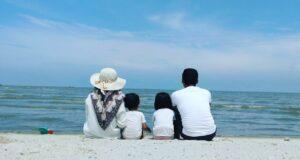 Keluarga tengah berfoto bersama berlatarkan birunya langit dan beralaskan putihnya pasir Sri Mersing