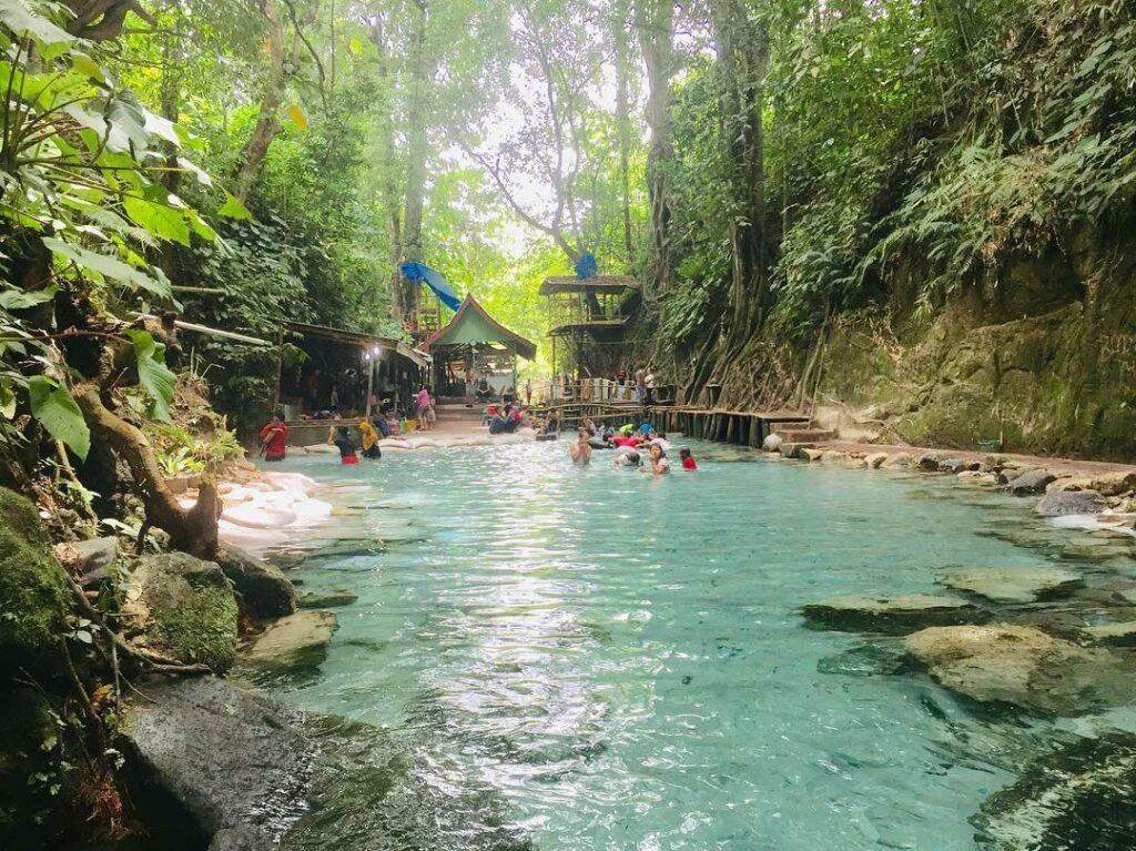 wisatawan sedang mandi di sungai yang sangat jernih