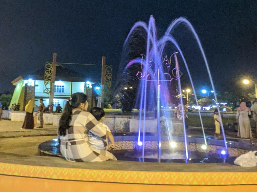 Melihat air mancur dengan sorotan lampu berwarna cerah di malam hari