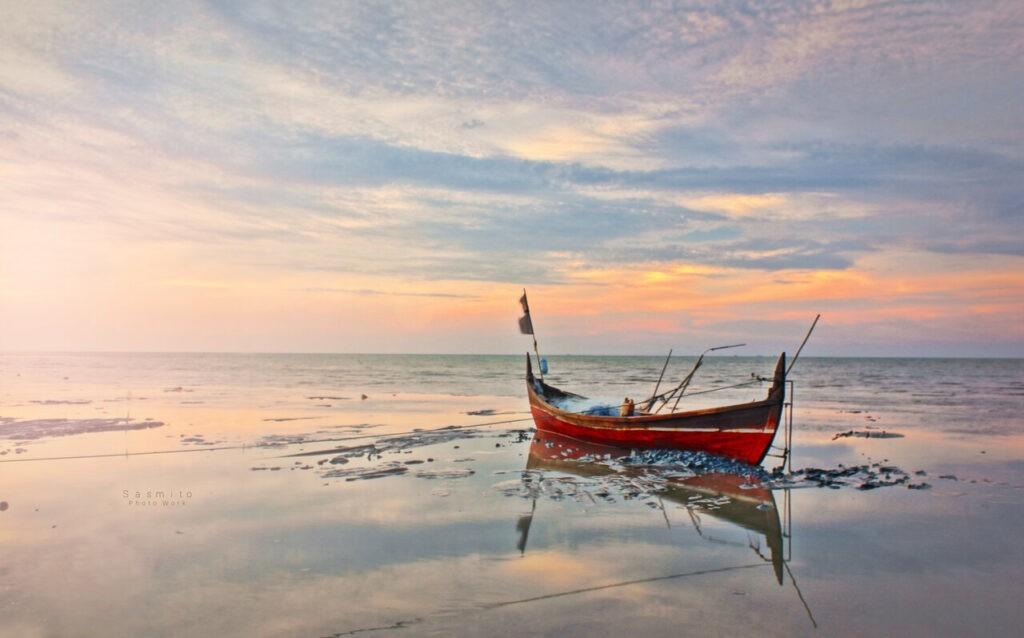Kapal nelayan yang tengah berlabuh di kala senja merupakan fenomena yang sering terlihat di Pantai Sri Mersing