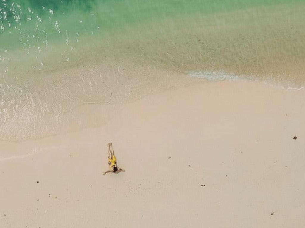 Hamparan pasir putih dan air biru kehijauan