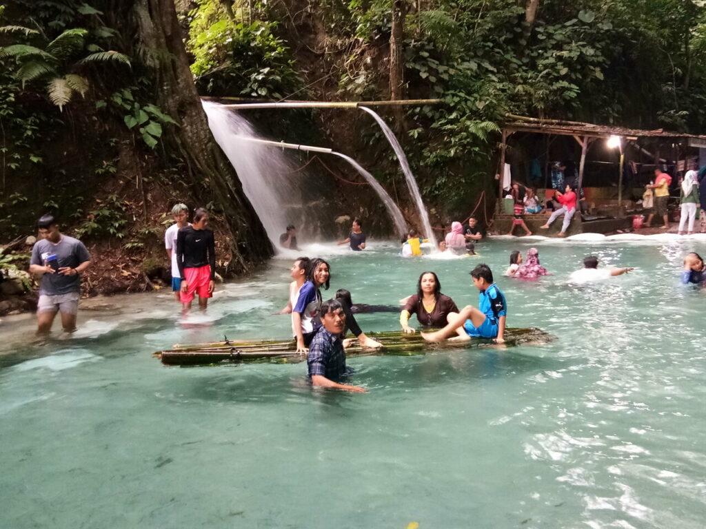 Selain berenang, pengunjung juga dapat bermain rakit di Pemandian Bah Damanik