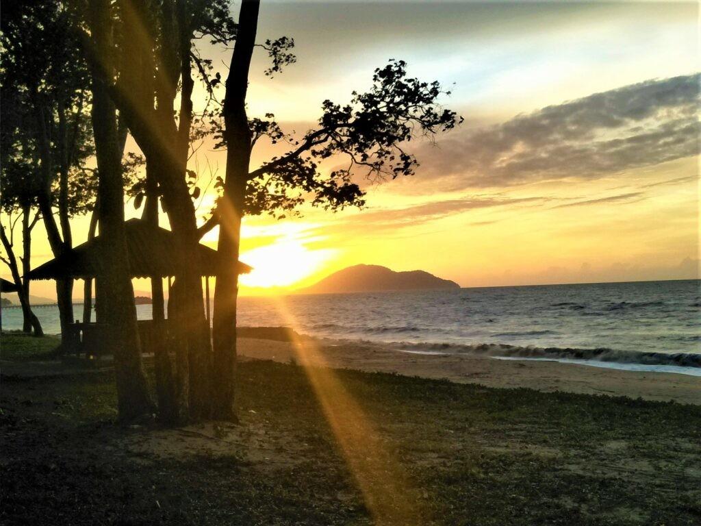 Menikmati matahari terbenam dari tepi pantai pasir panjang