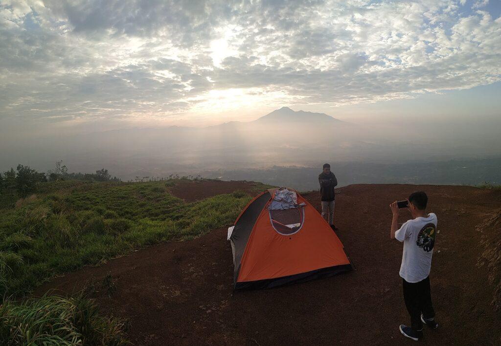 Wisatawan tengah Mengabadikan Foto dengan Latar Belakang Gunung Gede Pangrango