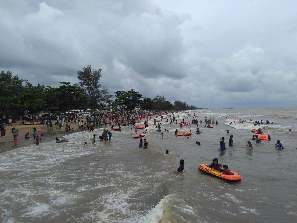 Ramai pengunjung bermain di tepi pantai