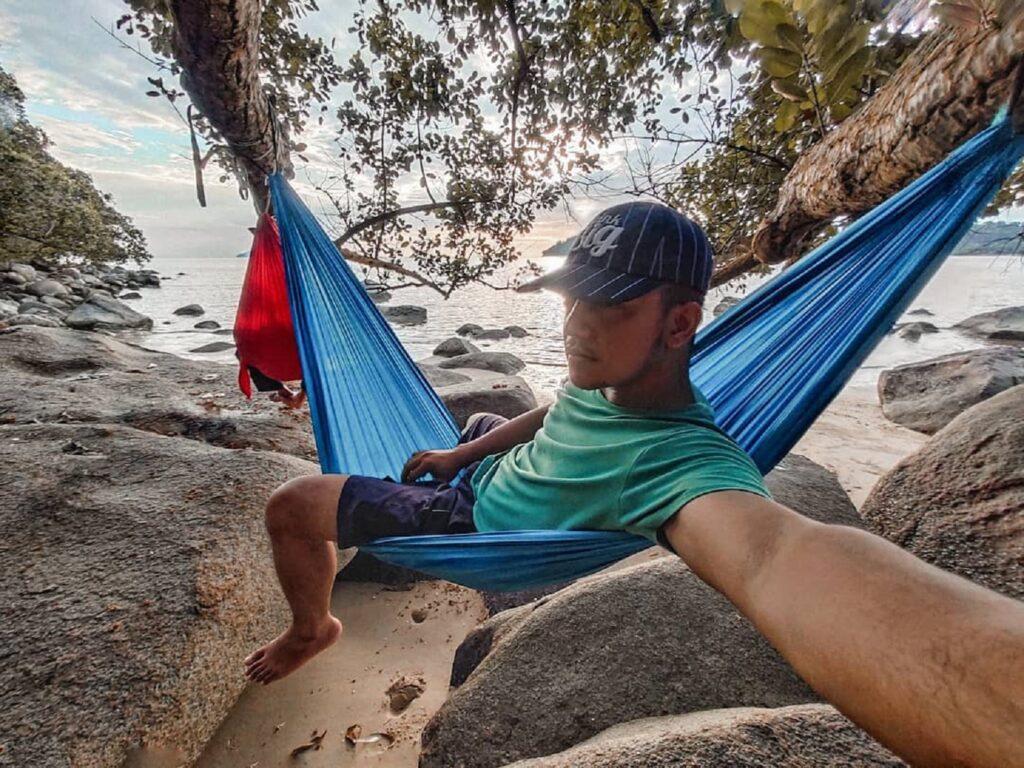 Bersantai di atas hammock di tepi Pantai
