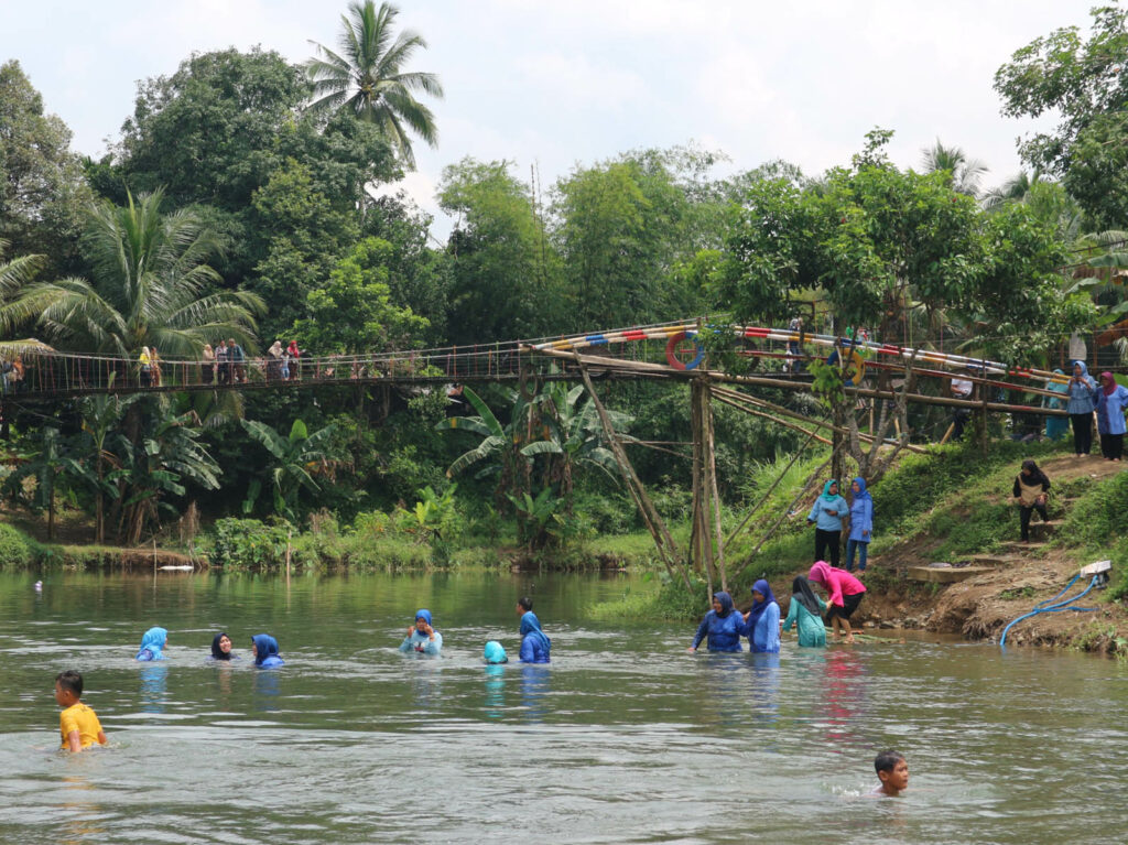 Pengunjung bisa bermain air di sungai yang jernih