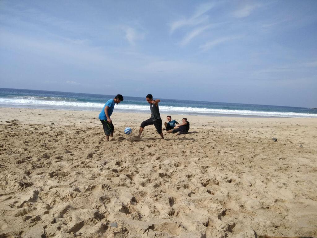 wisatawan sedang bermain sepak bola di tepi pantai