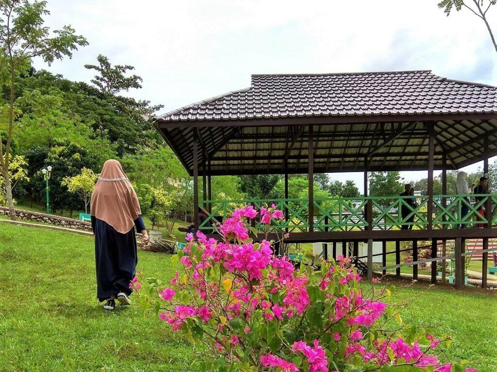 Area taman dipenuhi rumput dan bunga warna-warni