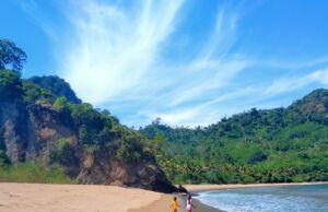 bentang alam pantai yang dikelilingi perbukitan hijau
