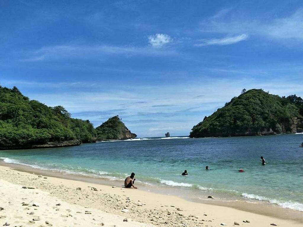 wisatawan berenang di perairan tepi pantai