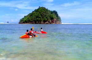 wisatawan bermain kano di area tepi pantai gatra