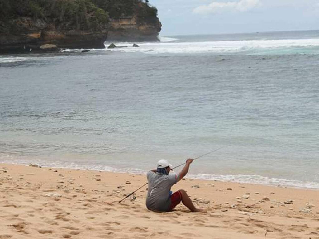 Pengunjung Menunggu hasil pancingan di tepi pantai.