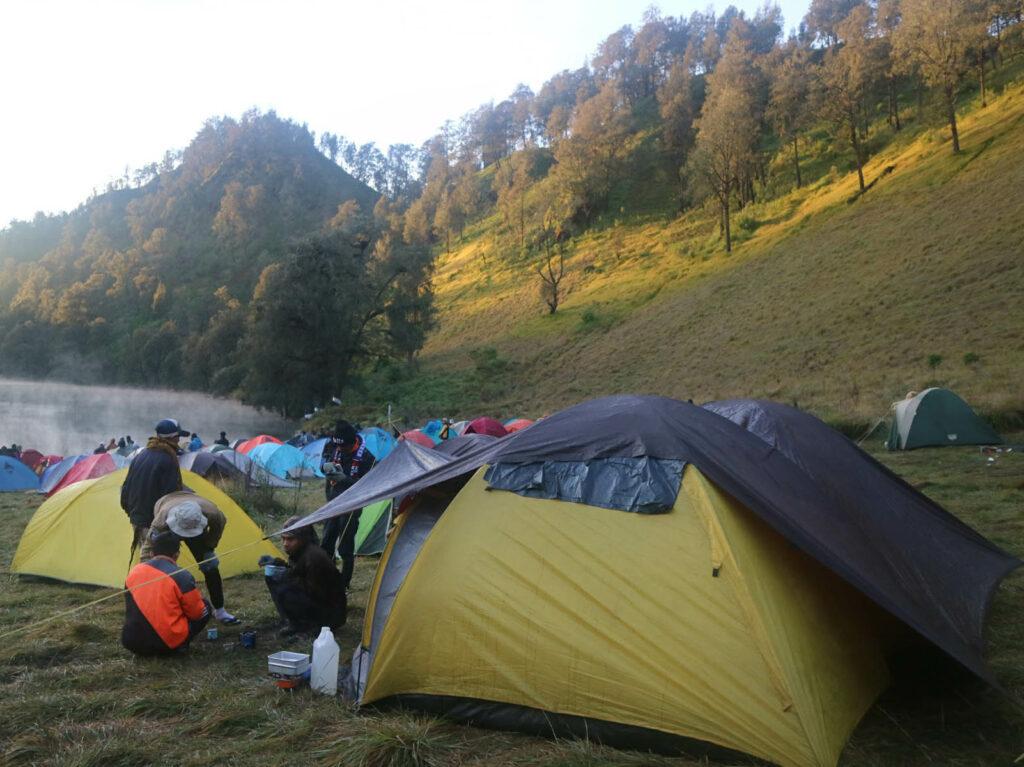 Pengunjung sedang mendirikan tenda di tepi danau
