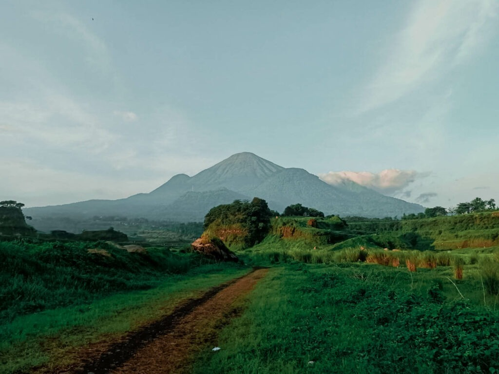 Hamparan padang rumput hijau Ranu Manduro berlatar gunung penanggungan