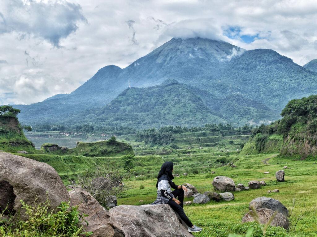 Berfoto dengan latar padang rumput dan pegunungan hijau Ranu Manduro