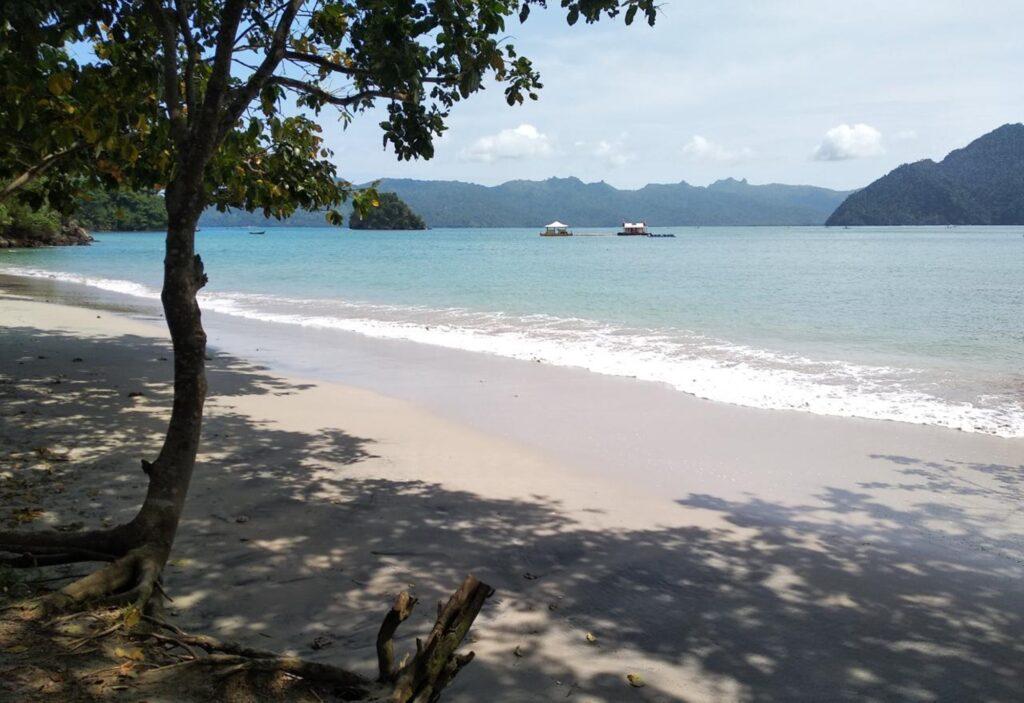 perpaduan hamparan pasir putih serta gradasi laut yang biru