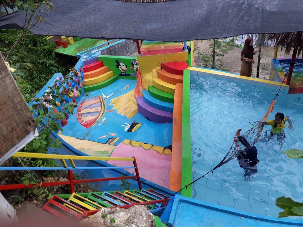 pengunjung asyik bermain air di salah satu kolam renang di Tebing Pelangi