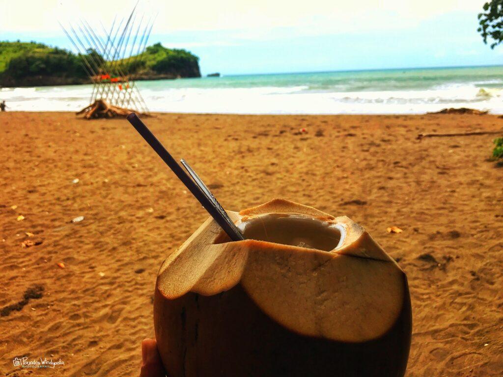 Pengunjung menikmati kelapa muda di pinggir pantai