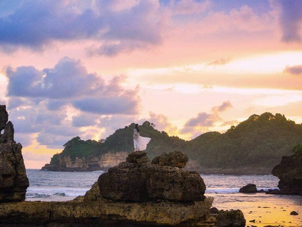 pengunjung berfoto di atas salah satu batu karang