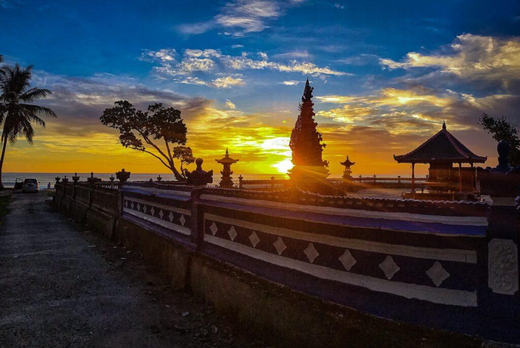 panorama matahari terbit dari balik Pura Tirta Bhuana