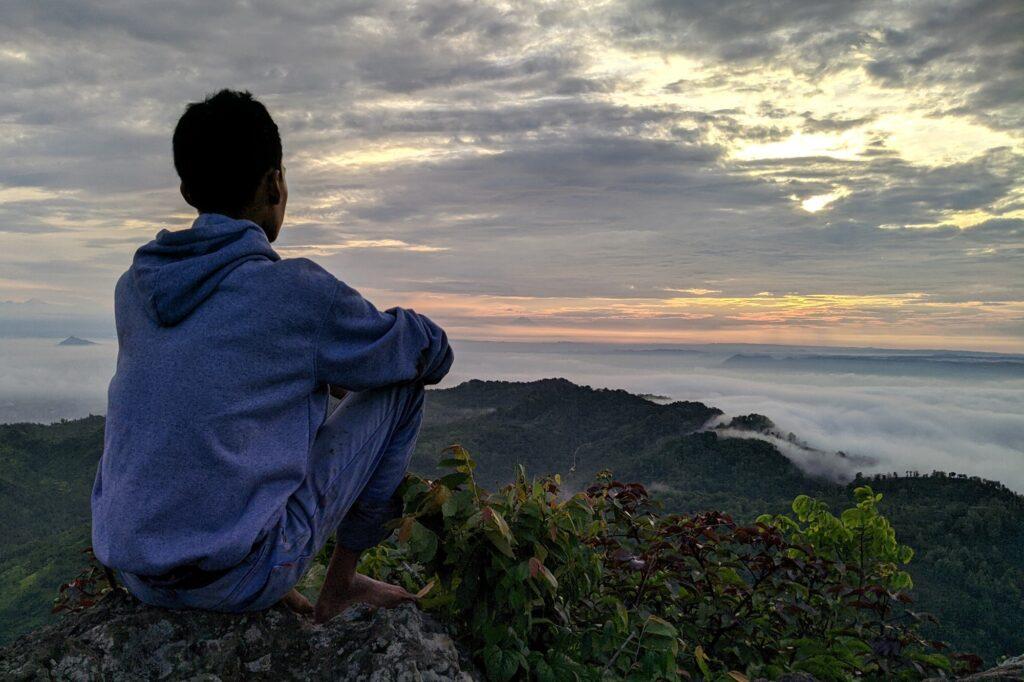 pendaki tengah menikmati suasana sambil menyaksikan matahari terbit