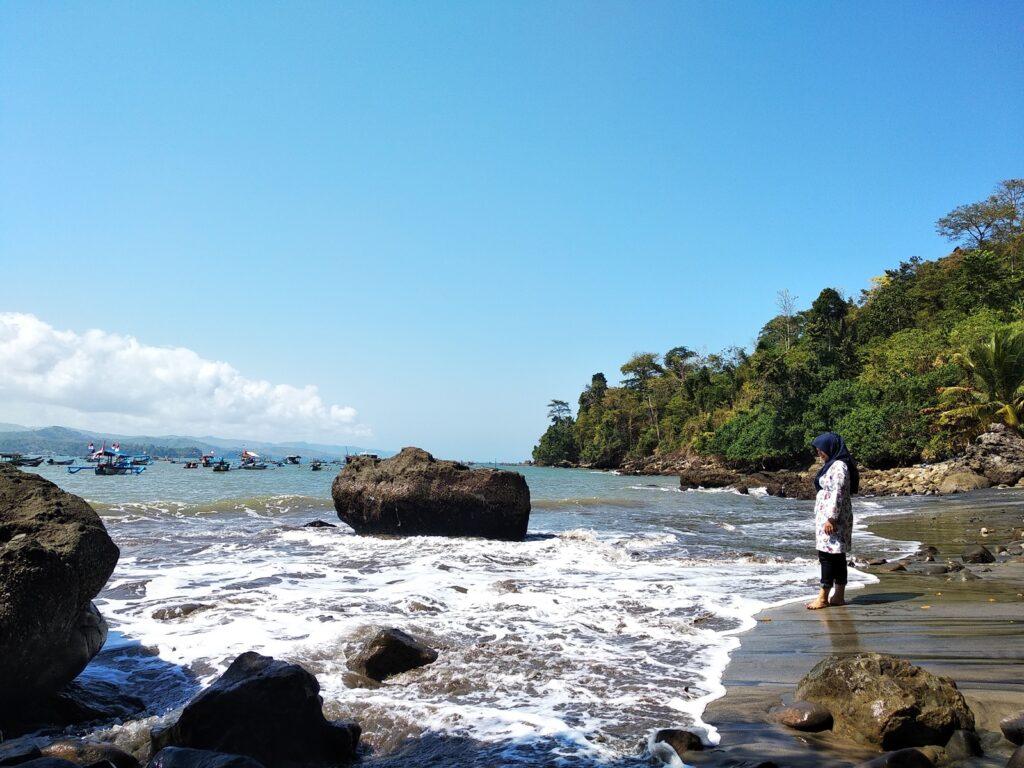 wisatawan bermain ombak di area bibir pantai
